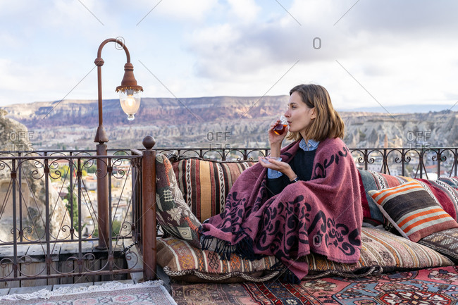 Woman is drinking tea on a balcony in Cappadocia, Turkey