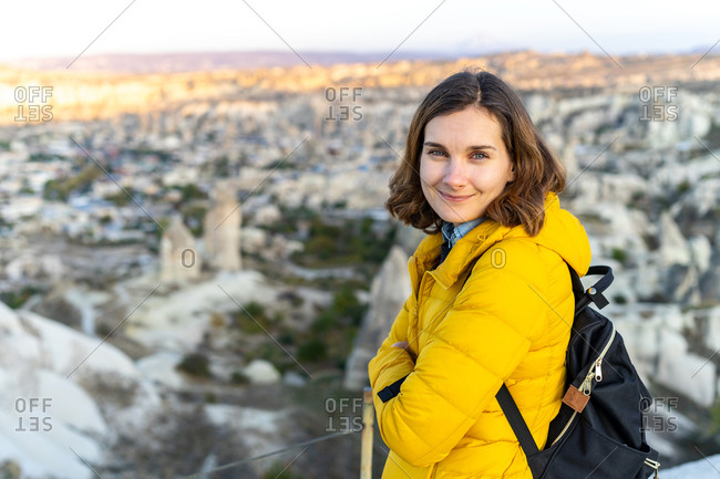 Woman traveler in bright yellow jacket at sunset in central Turkey