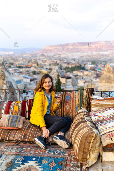 Woman is enjoying the glass of wine on the balcony at sunset