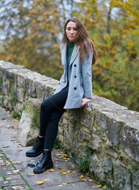 portrait of a young Caucasian woman with brown hair on a stone bridge with the green of the trees in the background. Dressed in a gray jacket, green sweater, dark pants and military boots