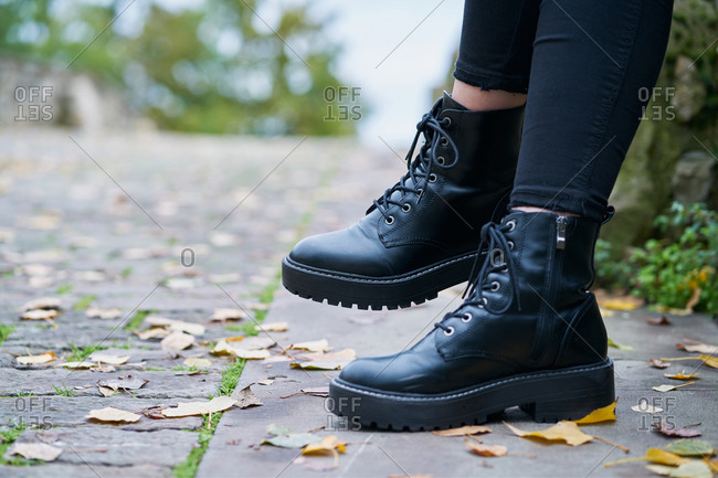 Close-up of the boots worn by a woman in military style in black with a stone floor background