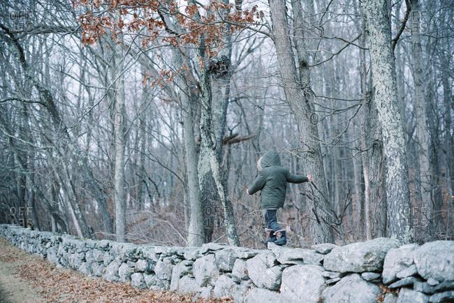 Two kids walking through a mowed meadow in winter.