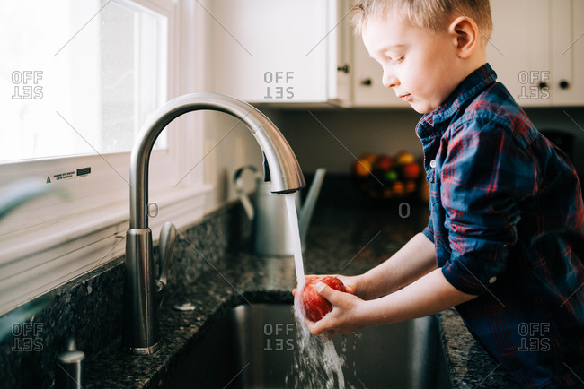 Little Toddler washing an apple before eating it.