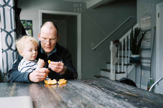Grandfather eating a mandarin orange with his grandson.