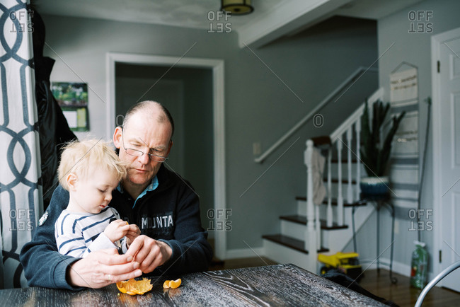 Grandfather and his grandson eating a mandarin orange together.
