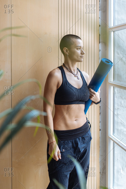 short haired athletic woman standing near window holding rolled yoga m