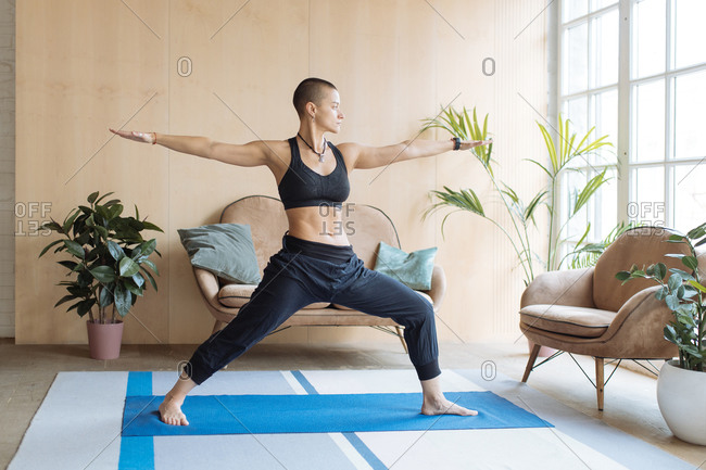 short haired athletic woman standing in yoga warrior pose in home loft