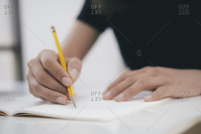 Close up hands with pen writing on notebook.