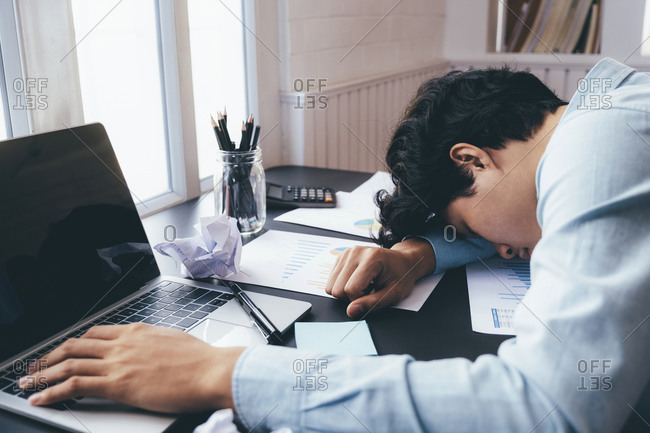 A young businessman who works hard and sleeps at his desk.