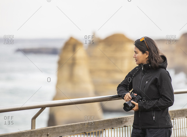 woman admiring the 12 apostles sea stacks in the south of Australia