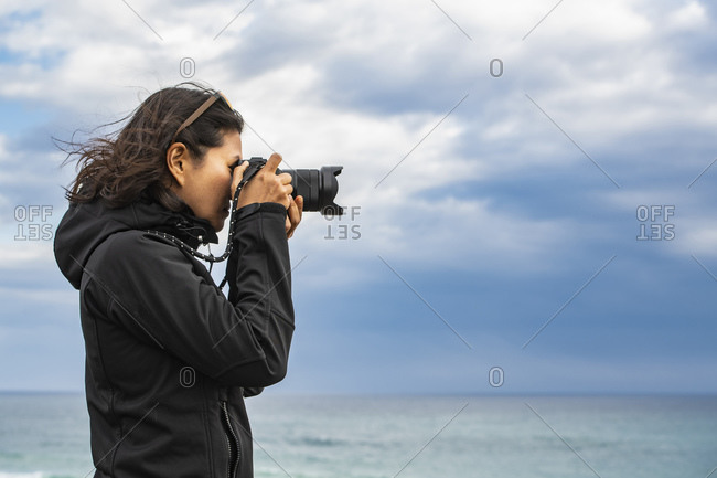 woman taking a photograph with a digital camera at the 12 Apostle's