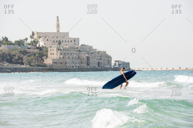 Surfs up as a female surfer heads into the waves in Israel