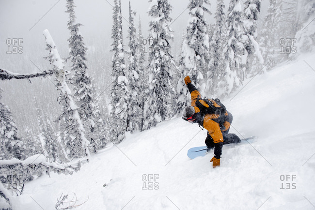 A male snowboarder finds deep powder in the Canadian backcountry.