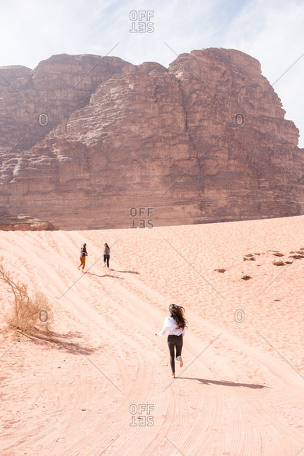 Three friends sprint to the horizon of the Wadi Rum desert in Jordan.