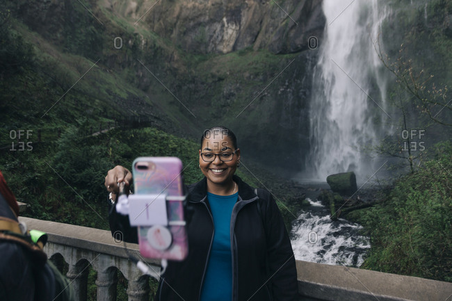 A woman takes a selfie at Multnomah Falls in the Columbia River Gorge.