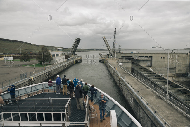 A group of tourists travel through the locks at a dam.