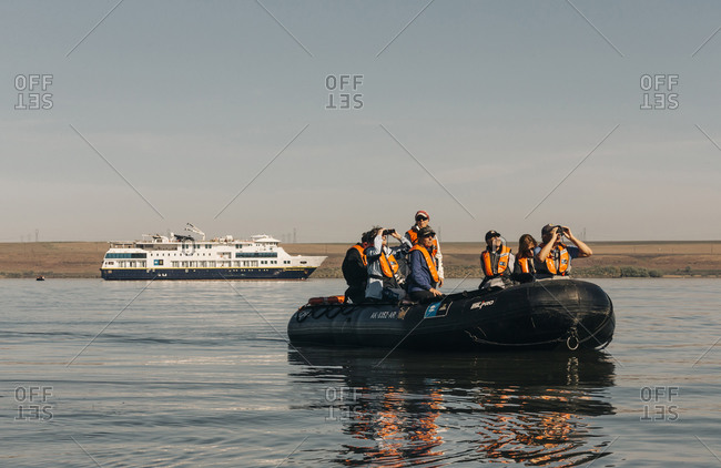 A group of tourists travel on a small boat on the Columba River.