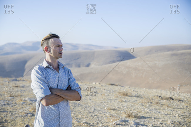 A man is standing alone in the desert, disturbed. Looking sideways