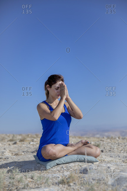 A woman is meditating in the desert