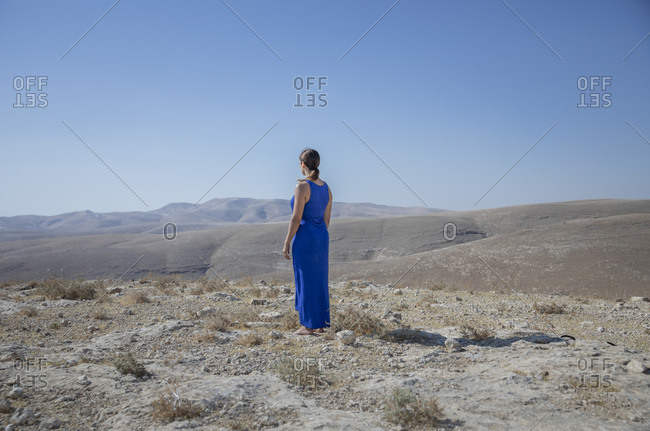 A woman is standing alone in the desert