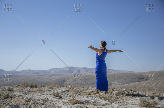 A woman is standing alone in the desert, arms wide open, hopeful