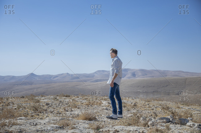 A man is standing alone in the desert, looking disturbed