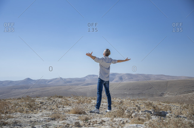 A man is standing alone in the desert, arms wide open, delighted