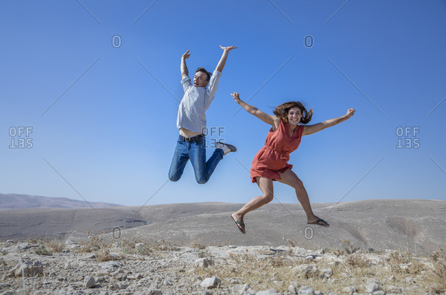 A man and a woman jumping in the air in the middle of the hot desert