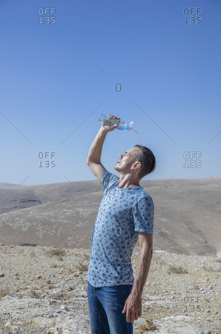 A man is pouring water over his head in the desert