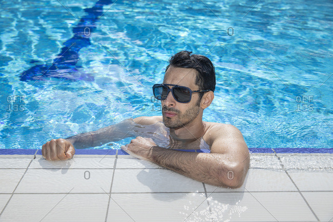 A man or a boy is looking out from inside a swimming pool