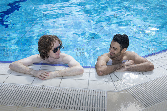 Two men or boys are talking inside the swimming pool