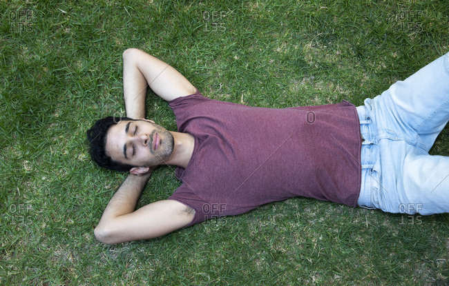 A man or a boy is sleeping or relaxing on the grass, hands behind his head