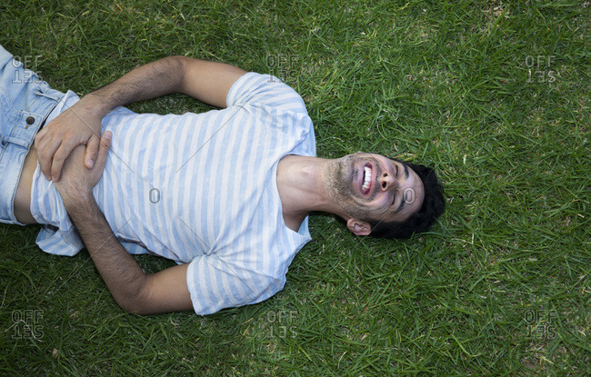 A man or a boy is laughing, lying on the grass