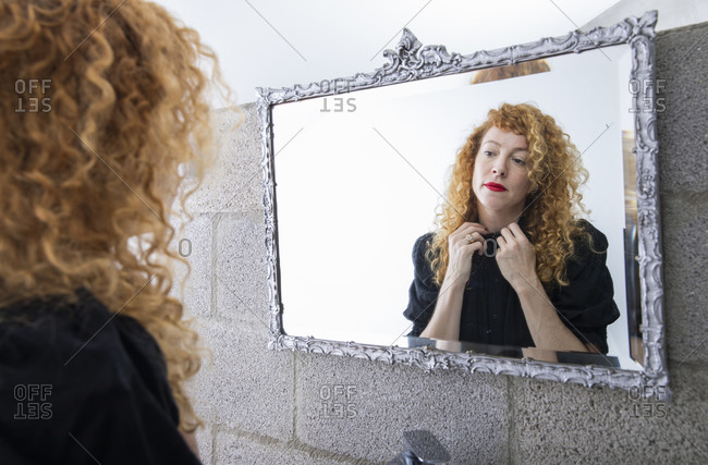 An adult woman looking at her mirror image in the bathroom