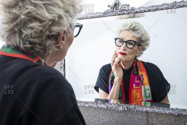 A senior woman looking at her mirror image in the bathroom