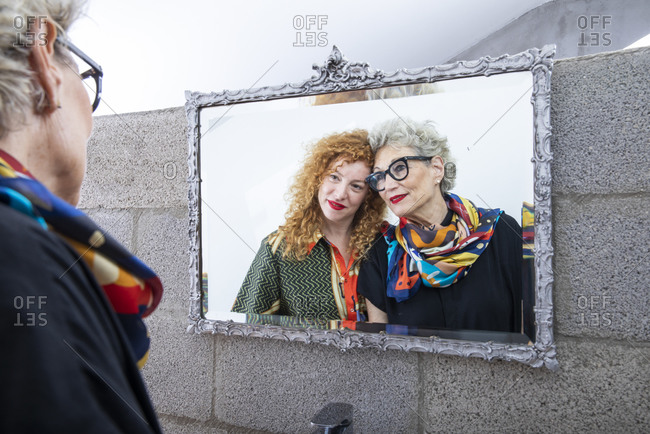 A senior mother and an adult daughter looking at their mirror image in the bathroom
