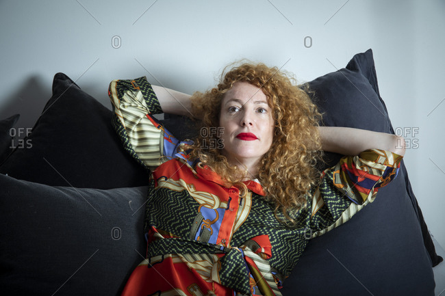 An adult woman is resting in the living room, looking up