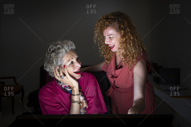 A senior woman and her adult daughter looking at a computer screen together, at the study, laughing