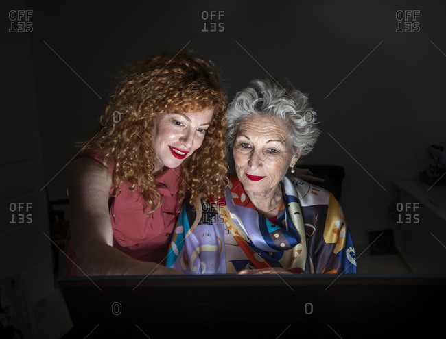 A senior woman and her adult daughter looking at a computer screen together, at the study.