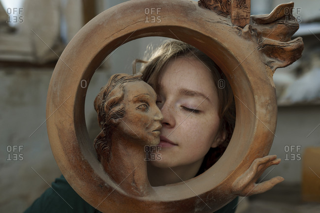 Young woman and circular wooden sculpture