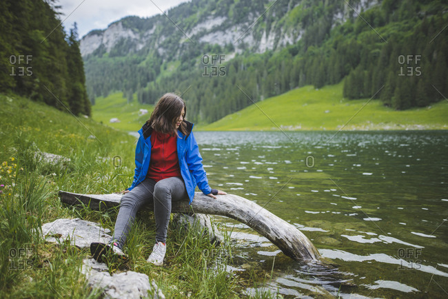 Young woman sitting on log by lake