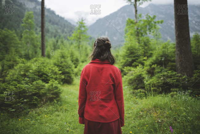 Young woman with red jacket in forest
