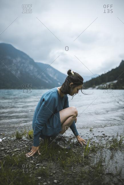 Young woman crouching by lake