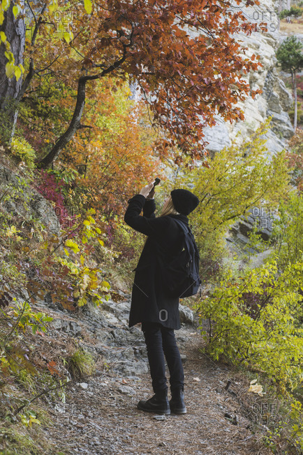 Young woman photographing with smartphone in autumn forest