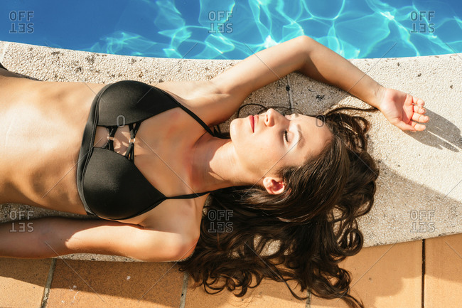 Portrait of a beautiful young woman lying on her back on the edge of a pool with a bikini in summer
