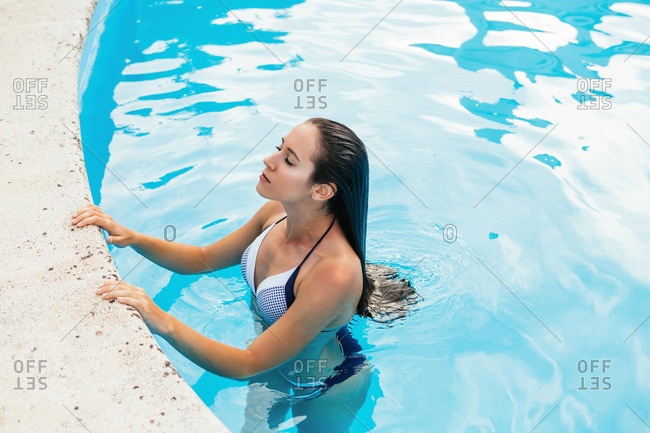 Summer portrait of a beautiful young woman inside a swimming pool