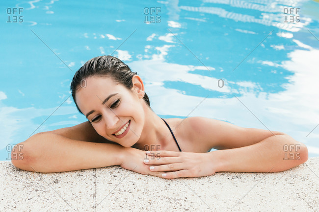 Summer portrait of a beautiful young woman smiling inside a swimming pool