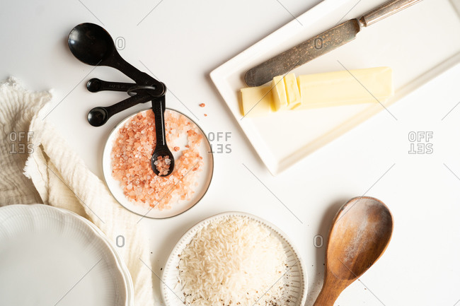 White rice, salt and butter on white countertop