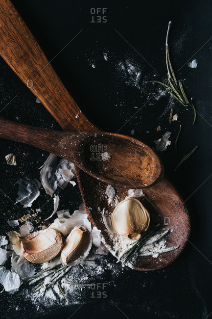 Garlic cloves and flour on wood spoons on dark surface