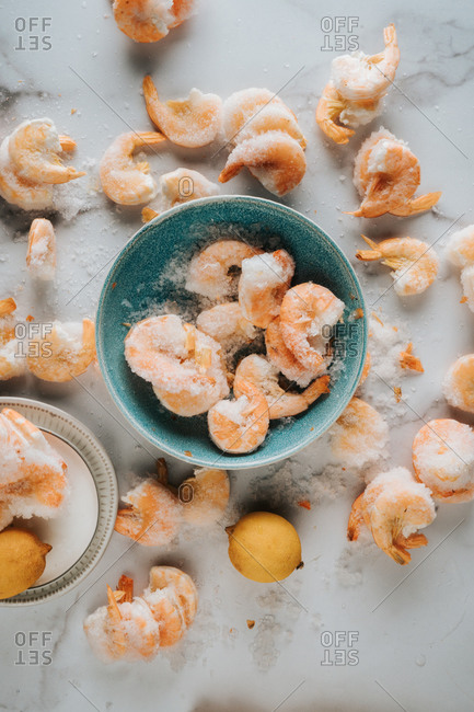 Frozen shrimp on a marble counter top with blue bowl
